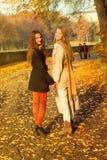 2 девушки идут в парк осени Стоковые Фотографии RF