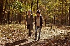 Девушки идя в лес осени в горах Пеший туризм и путешествовать Стоковая Фотография