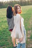 2 девушки идя outdoors на заход солнца Стоковая Фотография