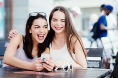 Девушки имеют потеху с телефоном в кофе Стоковые Фотографии RF