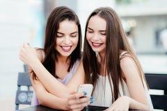 Девушки имеют потеху с телефоном в кофе Стоковое фото RF