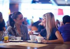 Девушки имеют чашку кофе в ресторане Стоковое Изображение