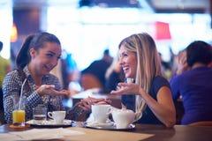 Девушки имеют чашку кофе в ресторане Стоковые Фото