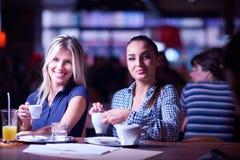 Девушки имеют чашку кофе в ресторане Стоковые Изображения
