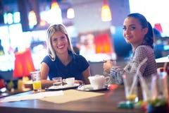 Девушки имеют чашку кофе в ресторане Стоковая Фотография