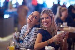 Девушки имеют чашку кофе в ресторане Стоковое Изображение RF