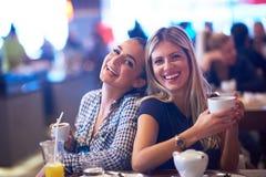 Девушки имеют чашку кофе в ресторане Стоковые Фотографии RF
