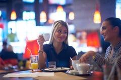 Девушки имеют чашку кофе в ресторане Стоковое Фото