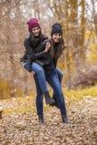 2 девушки имея потеху в парке осени Стоковое Фото