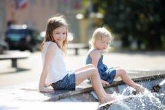 Девушки имея потеху в фонтане Стоковое Фото