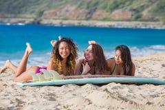 3 девушки имея потеху на пляже с surboard Стоковые Фотографии RF