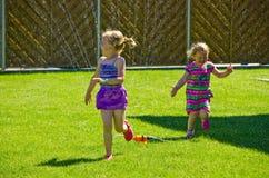 Девушки имея потеху с спринклером в саде Стоковые Изображения RF