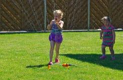 Девушки имея потеху с спринклером в саде Стоковые Изображения