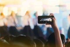 Девушки используют смартфоны для того чтобы сфотографировать на концертах стоковые изображения rf