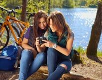 2 девушки используя компактную камеру фото на одичалом реке плавают вдоль побережья Стоковая Фотография