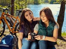 2 девушки используя компактную камеру фото на одичалом реке плавают вдоль побережья Стоковые Фотографии RF