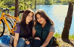 2 девушки используя компактную камеру фото на одичалом реке плавают вдоль побережья Стоковое Изображение RF