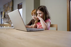Девушки используя компьтер-книжку на таблице Стоковые Изображения