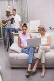 Девушки используя компьтер-книжку с мальчиками на заднем плане Стоковое Изображение