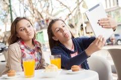Девушки используя таблетку в улице Стоковое фото RF