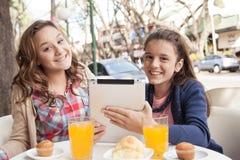 Девушки используя таблетку в улице Стоковое Изображение