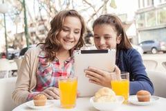 Девушки используя таблетку в улице Стоковая Фотография RF