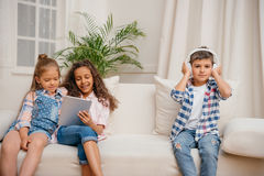 Девушки используя таблетку пока музыка мальчика слушая в наушниках Стоковая Фотография RF