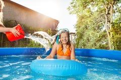 Девушки лить воду от красного ведра в бассейне Стоковые Фотографии RF