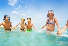 Девушки и мальчики бежать в мелководье совместно Стоковые Изображения RF
