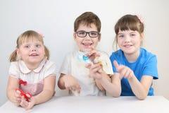2 девушки и мальчик играют с обтекателями втулки на таблице Стоковые Изображения