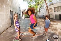 Девушки и мальчик играют эластичную игру веревочки совместно Стоковое Изображение