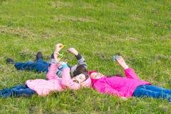2 девушки и мальчик лежат на траве и обтекателе втулки игры Стоковая Фотография