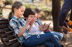 Девушки и мальчик с smartphones на стенде в парке в осени Стоковые Фото