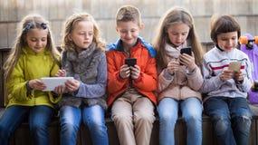 Девушки и мальчик с smartphones на стенде в парке Стоковое Фото