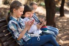 Девушки и мальчик с smartphones на стенде в парке Стоковая Фотография RF