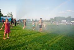 Девушки и мальчики играя в дожде внешнем Стоковое фото RF
