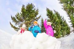 Девушки и мальчик играя игру снежных комьев в лесе Стоковые Фото