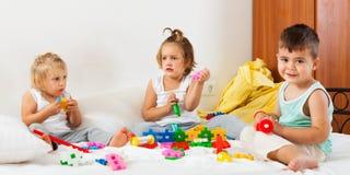 Девушки и мальчик играя на большой кровати Стоковая Фотография