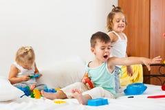 Девушки и мальчик играя на большой кровати Стоковое Фото