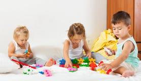 Девушки и мальчик играя на кровати Стоковые Фотографии RF