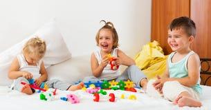 Девушки и мальчик играя на кровати Стоковое Фото