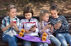 Девушки и мальчик с smartphones на стенде в парке в осени Стоковая Фотография