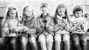 Девушки и мальчик с smartphones на стенде в парке Стоковое Изображение RF