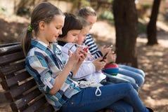 Девушки и мальчик с smartphones на стенде Стоковое Изображение RF