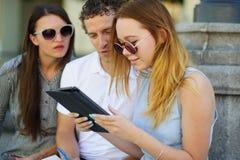 2 девушки и парень с интересом смотрят экран таблетки Стоковое Фото
