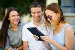 2 девушки и парень с интересом смотрят экран таблетки Стоковое Изображение