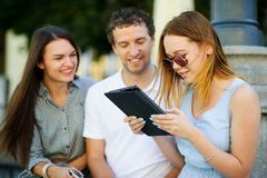 2 девушки и парень с интересом смотрят экран таблетки Стоковые Изображения RF