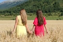 Девушки идут в поле для рук Стоковое Изображение