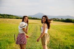 Девушки идя в зеленый луг Стоковые Изображения