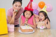 Девушки и noisemakers матери дуя на вечеринке по случаю дня рождения Стоковое фото RF
